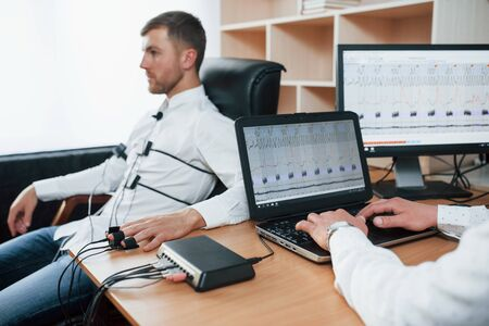 Tense look. Suspicious man passes lie detector in the office. Asking questions. Polygraph test. Фото со стока