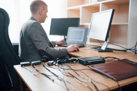 Profesional está en el trabajo. Examinador de polígrafo en la oficina con el equipo de su detector de mentiras.