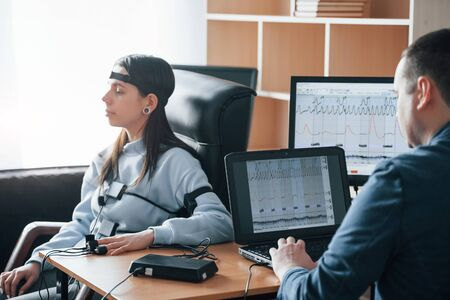 Calm woman. Girl passes lie detector in the office. Asking questions. Polygraph test. Фото со стока
