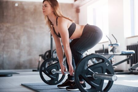 Doing squating with black barbell. Photo of gorgeous blonde woman in the gym at her weekend time. Stock Photo