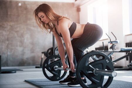 Strong girl. Photo of gorgeous blonde woman in the gym at her weekend time. Stock Photo