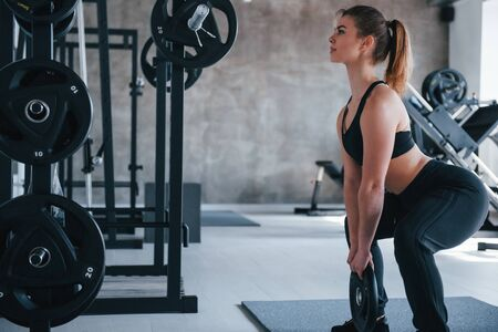 Keep holding on. Photo of gorgeous blonde woman in the gym at her weekend time. Stock Photo