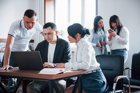 Geconcentreerd op het werk. Mensen uit het bedrijfsleven en manager werken aan hun nieuwe project in de klas.