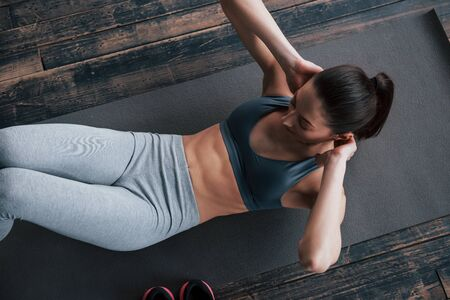 Standard exercise but so effective. Top view of girl with slender body works on the abs when lying on the floor.