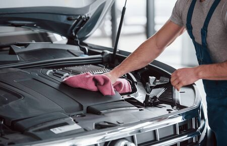 Cleaning after nice job. Man in blue uniform works with broken car. Making repairings.