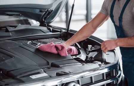 Reinigung nach schöner Arbeit. Mann in blauer Uniform arbeitet mit kaputtem Auto. Reparaturen vornehmen.