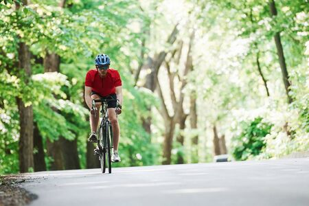 Bearded man. Cyclist on a bike is on the asphalt road in the forest at sunny day.