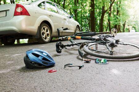 Lieu dangereux. Vélo et accident de voiture de couleur argentée sur la route en forêt pendant la journée. Banque d'images