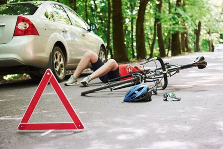 Man lying down. Victim on the asphalt. Bicycle and silver colored car accident on the road at forest at daytime. 스톡 콘텐츠