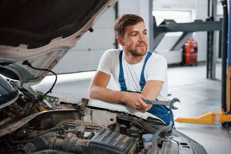 Bonne humeur. L'employé en uniforme de couleur bleue travaille dans le salon automobile.
