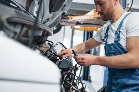 Trust your repairman. Employee in the blue colored uniform works in the automobile salon. Stockfoto