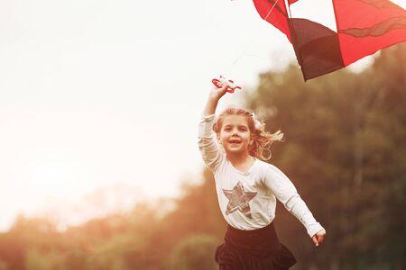 Erstaunliches Sonnenlicht. Glückliches Mädchen in Freizeitkleidung, das mit Drachen im Feld läuft. Schöne Natur. Standard-Bild