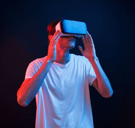 This is breathtaking. Young man using virtual reality glasses in the dark room with neon lighting.