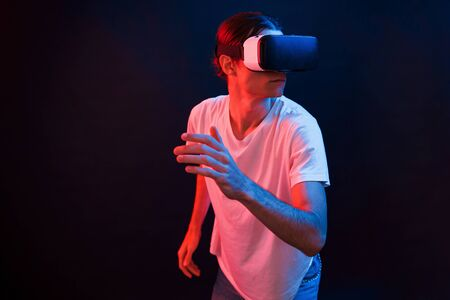Active leisure. Young man using virtual reality glasses in the dark room with neon lighting.