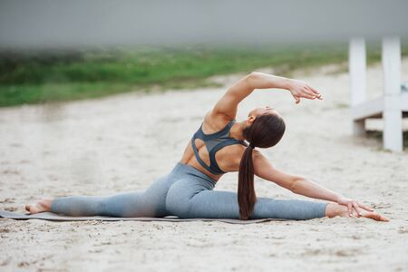 View from behind. Brunette with nice body shape in sportive clothes have fitness day on a beach. Stock Photo