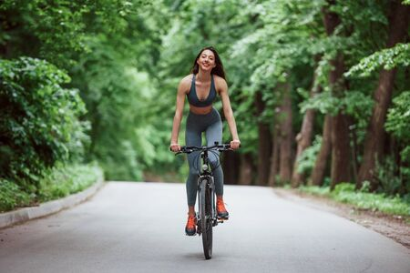 Female cyclist on a bike on asphalt road in the forest at sunny day.
