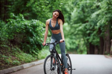 Smiling and feeling good. Female cyclist on a bike on asphalt road in the forest at daytime.