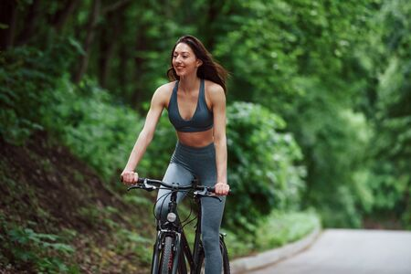 Cheerful mood. Female cyclist on a bike on asphalt road in the forest at daytime.