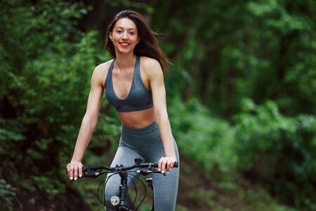 Front view. Female cyclist on a bike on asphalt road in the forest at daytime. Stock fotó