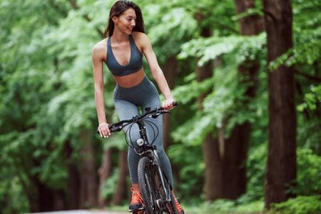 Happy brunette. Female cyclist on a bike on asphalt road in the forest at daytime.