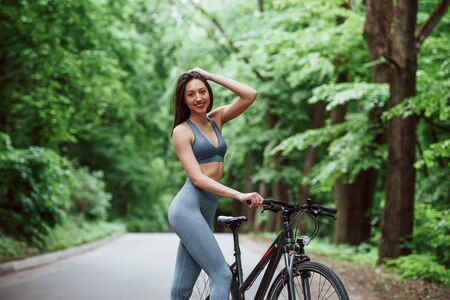 Posing for a camera. Female cyclist standing with bike on asphalt road in the forest at daytime.