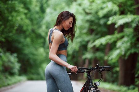 Looking at vehicle. Female cyclist standing with bike on asphalt road in the forest at daytime. 스톡 콘텐츠