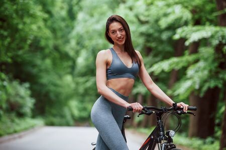 Finally its summer. Female cyclist standing with bike on asphalt road in the forest at daytime. Stock fotó - 135495026