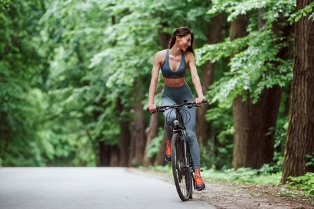With smile on the face. Female cyclist on a bike on asphalt road in the forest at daytime. 스톡 콘텐츠