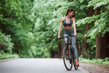 Having trip. Female cyclist on a bike on asphalt road in the forest at daytime.