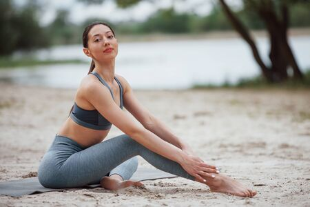Lake behind. Brunette with nice body shape in sportive clothes have fitness day on a beach.