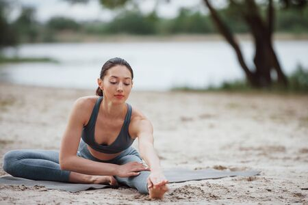 Easy warm-up. Brunette with nice body shape in sportive clothes have fitness day on a beach.