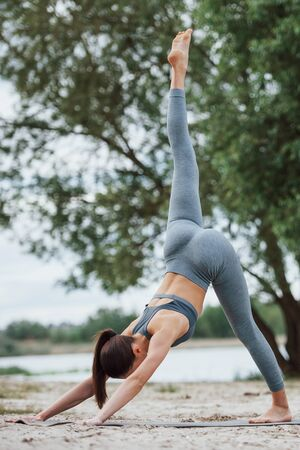 Vertical photo. Brunette with nice body shape in sportive clothes have fitness day on a beach.