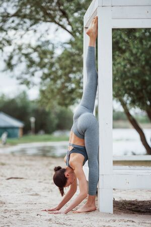 Nice stretch. Brunette with nice body shape in sportive clothes have fitness day on a beach.