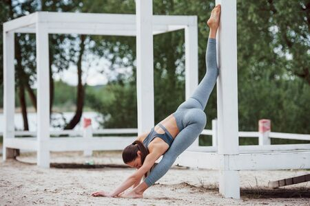 Long legs and nice stretching. Brunette with nice body shape in sportive clothes have fitness day on a beach.