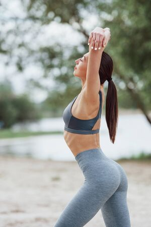 Slim body type. Brunette in sportive clothes have fitness day on a beach. Stock Photo