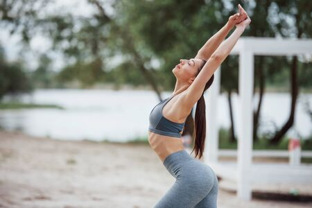 With hands up. Brunette with nice body shape in sportive clothes have fitness day on a beach. Stock Photo