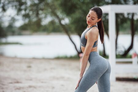 Showing body. Brunette in sportive clothes have fitness day on a beach.