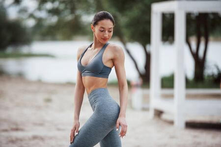 Alone in the park. Brunette with nice body shape in sportive clothes have fitness day on a beach. Stock fotó