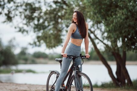 Feeling good to be here. Female cyclist with good body shape standing with her bike on beach at daytime. Stock fotó