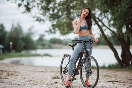 I love this place. Female cyclist with good body shape standing with her bike on beach at daytime.