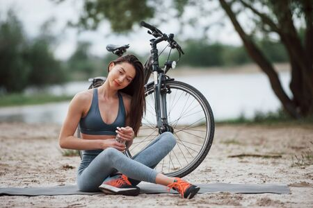 Opening bottle with water. Female cyclist with good body shape sitting near her bike on beach at daytime.