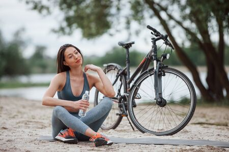 Thoughtful look. Female cyclist with good body shape sitting near her bike on beach at daytime.