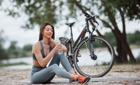 Drinking water. Female cyclist with good body shape sitting near her bike on beach at daytime.