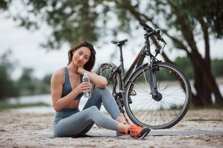 Water is very important. Female cyclist with good body shape sitting near her bike on beach at daytime.