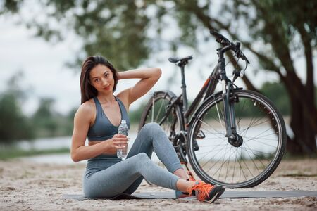 Touching the hair. Female cyclist with good body shape sitting near her bike on beach at daytime.