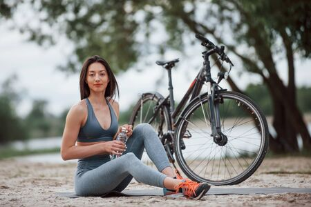 Do not forget take water for your exersices. Female cyclist with good body shape sitting near her bike on beach at daytime. 스톡 콘텐츠