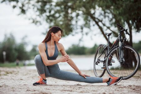 Concentrated look. Female cyclist with good body shape doing yoga exercises and stretching near her bike on beach at daytime.