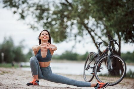 This exercise will make you more flexible. Female cyclist with good body shape doing yoga and stretching near her bike on beach at daytime.