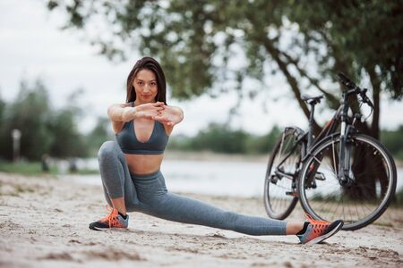 Variety of exercises. Female cyclist with good body shape doing yoga and stretching near her bike on beach at daytime. Stock fotó - 135494925