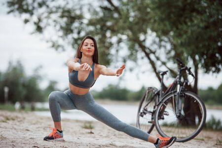 Doing squatting. Female cyclist with good body shape doing yoga exercises and stretching near her bike on beach at daytime. 스톡 콘텐츠